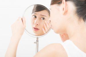 肌トラブルを鏡でチェックする女性